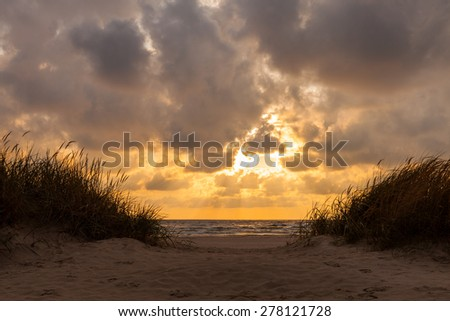 Dramatic cloudy sunset over Baltic sea coast in Liepaja, Latvia. There are sandy beach with dunes covered with grass in foreground. - stock photo