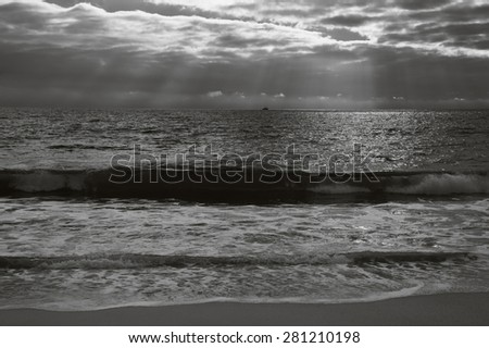 Dramatic cloudy sunset with sunbeams over Atlantic Ocean coast. Fishing ship sailing on horizon under sun rays glowing through the clouds. Nazare, Portugal. Aged photo. Black and white. - stock photo