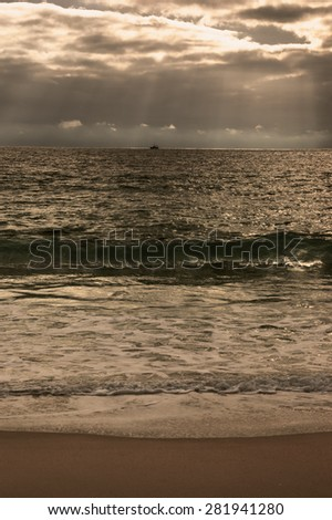 Dramatic cloudy sunset with sunbeams over Atlantic Ocean. Fishing ship (surrounded by flock of seagulls) sailing on horizon in sunrays glowing through the clouds. Nazare, Portugal. Toned photo.  - stock photo