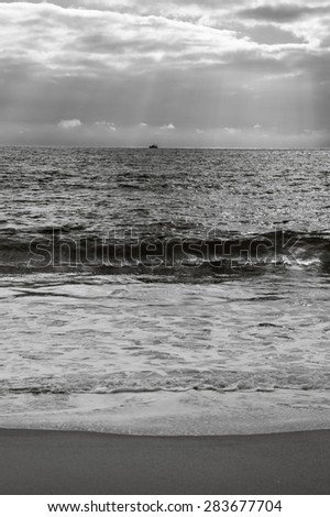 Dramatic cloudy sunset with sunbeams over Atlantic Ocean. Fishing ship (surrounded by flock of seagulls) sailing on horizon in sunrays glowing through the clouds. Nazare, Portugal. Black and white. - stock photo