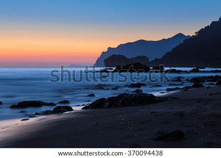 Dramatic coastal sunset on  rocky beach; low shutter speed - stock photo