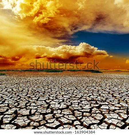 dramatic color clouds over drought earth - stock photo