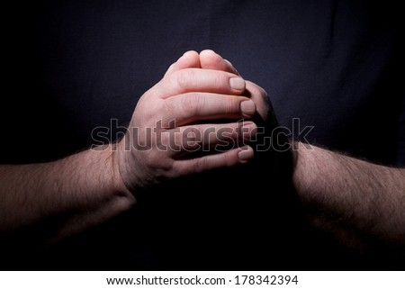 Dramatic contrast hands close up of praying middle aged man