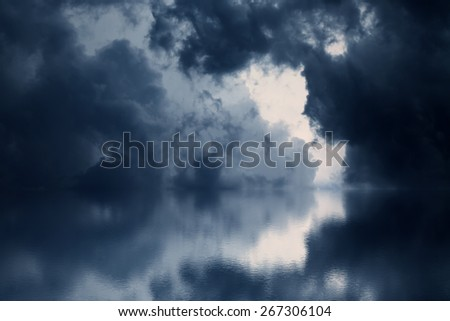 Dramatic dark clouds rise above the sea. Blue watercolor. - stock photo