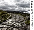Dramatic depiction of the dry stone hikers path leading to the summit of Mount Snowdon, under a stormy sky, Snowdonia, North Wales. - stock photo
