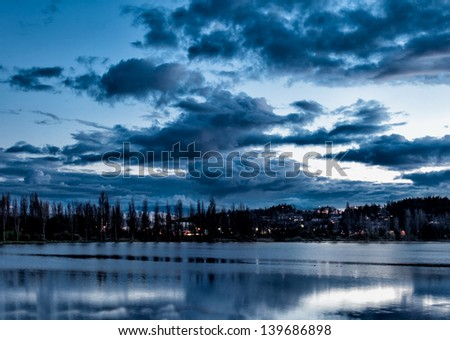 Dramatic evening sky with clouds over a lake with beautiful reflections - stock photo