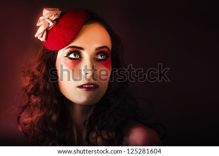 Dramatic Fashion Photo Of A Beautiful Brunette Woman Wearing Elegant Makeup And Spring Carnival Fascinator With Beautiful Red Makeup And Creative Hairstyle - stock photo
