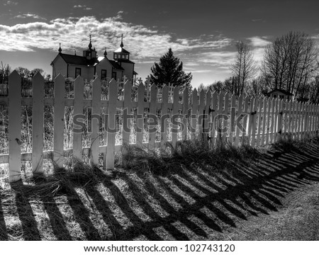 Dramatic fence shadows with the Russian orthodox church in Nikiski Alaska in black and white.