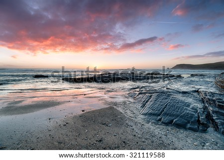 Dramatic fiery sunset at Booby's Bay on the edge of Constantine Bay on the Atlantic coast of Cornwall - stock photo