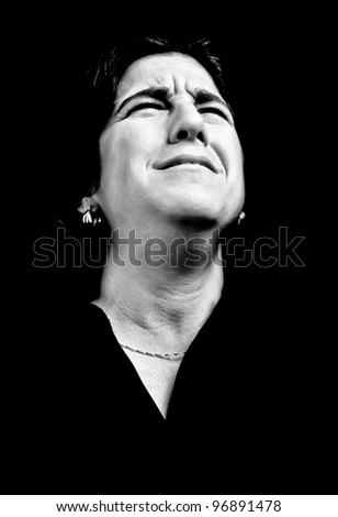 Dramatic high contrast portrait of a very sad and depressed woman on a black background - stock photo