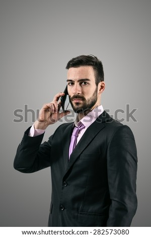 Dramatic high contrast portrait of serious confident business man talking on the cellphone over dark gray background with vignette.