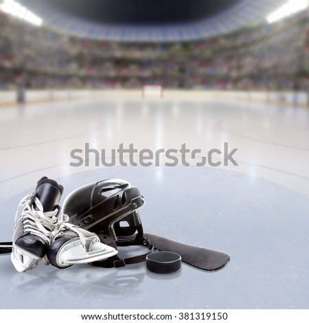 Dramatic Hockey arena full of fans in the stands with helmet, skates, stick and puck on reflective ice and copy space. Deliberate focus on equipment and shallow depth of field on background. - stock photo