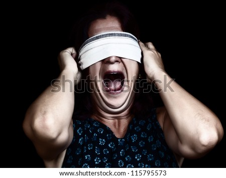 Dramatic image of a frightened woman screaming   and covering her eyes to avoid seeing isolated on black (useful to illustrate crime, gender violence or discrimination)