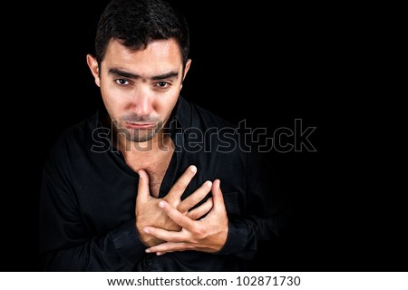 Dramatic image of a young man having a very painful heart attack bending over and clutching his chest isolated on black - stock photo