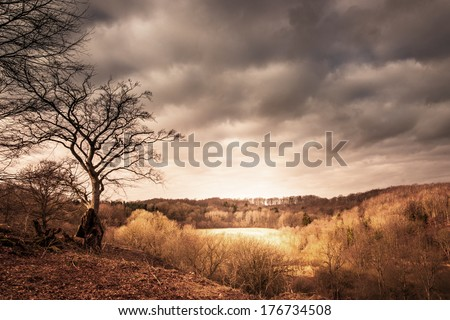 Dramatic landscape of a valley with sunshine shining through dark clouds - stock photo