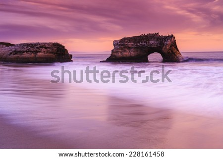 Dramatic landscape on a beach with rocks and an arch with glassy wave - stock photo