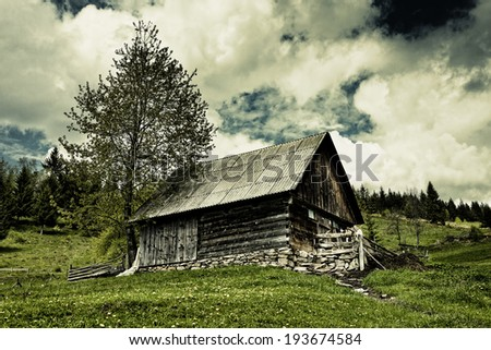 Dramatic landscape with an old barn on a meadow and moody sky - stock photo