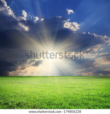 Dramatic landscape with field of green grass, stormy cloudy sky and sunlight - stock photo