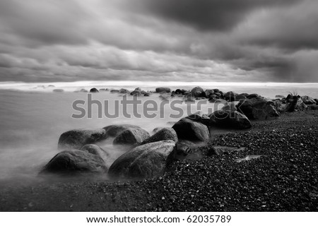 Dramatic landscape with rock coast and bad weather clouds in sky - stock photo