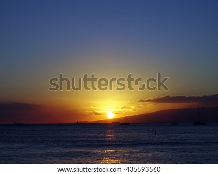 Dramatic lighting as Sunsets behind Waianae mountains with light reflecting on ocean and illuminating the sky with boats sailing on the water off Waikiki on Oahu, Hawaii. August 2015. - stock photo
