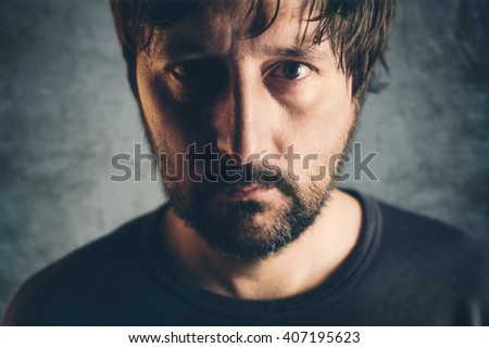 Dramatic low key portrait of adult male, headshot of sad lonely unshaven person, selective focus