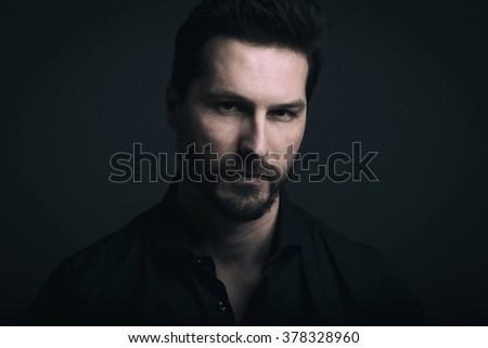 Dramatic man close up low key portrait against dark background. Digital manipulation to simulate film grain. - stock photo