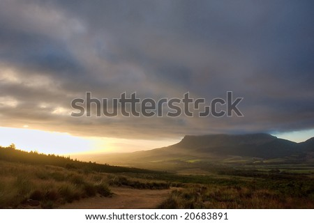 Dramatic mountain landscape in sunset light. Shot in Hottentots-Holland Mountains nature reserve, near Somerset West/Cape Town, Western Cape, South Africa. - stock photo