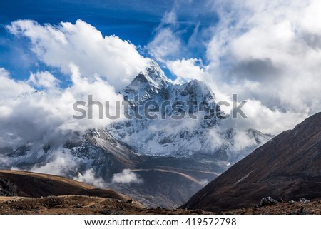 Dramatic mountain view of Ama Dablam summit on the famous Everest Base Camp trek in Himalayas, Nepal. Dramatic mountain landscape on a cloudy day. White clouds surrounding dramatic mountain summit. - stock photo