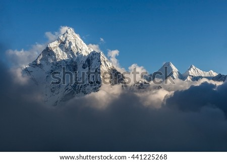 Dramatic mountain view of Ama Dablam summit on the famous Everest Base Camp trek in Himalayas, Nepal. Dramatic mountain landscape on a cloudy day. Grey clouds surrounding mountain summit. - stock photo