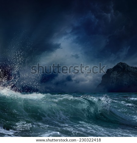 Dramatic nature background - big wave and dark rock in stormy sea, stormy weather - stock photo