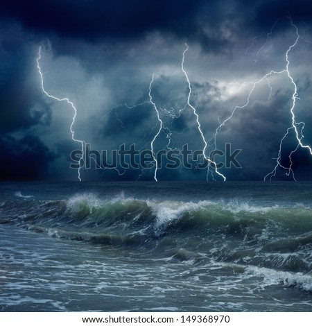 Dramatic nature background - lightnings in dark sky, stormy sea, big waves - stock photo
