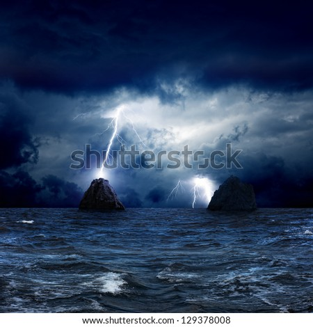 Dramatic nature background - lightnings in dark sky, two rocks in stormy sea - stock photo