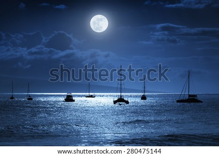 Dramatic night time photo illustration of a deep midnight blue sky with, bright full moon, over calm ocean waves in Maui, Hawaii.   Would make a great travel or vacation background. - stock photo