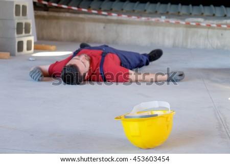 Dramatic on-the-job injury main focus on the yellow helmet - stock photo