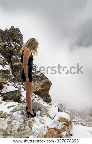 Dramatic photo of a beautiful girl standing on the edge of an abyss high in the snowy mountains. She is looking down. Stormy weather with falling snow
