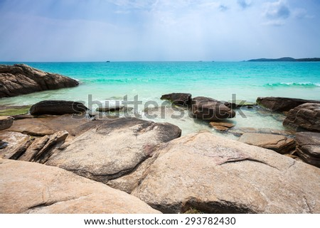 Dramatic photo of beautiful tropical beach- rocks in front of ocean on sunny day
