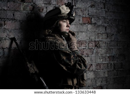 Dramatic portrait of a beautiful girl in uniform. Women in the military. U.S. Marines. Thoughts about the war. Young soldier. The spirit of liberty. - stock photo