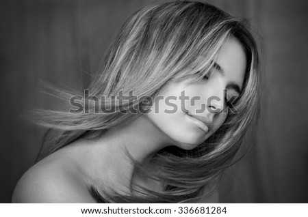 Dramatic portrait of a beautiful lonely girl with flying hair in the wind isolated on dark background, black and white photography