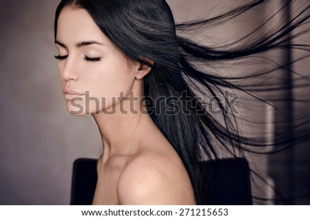 Dramatic portrait of a girl theme: portrait of a beautiful girl with flying hair in the wind against a background in the studio