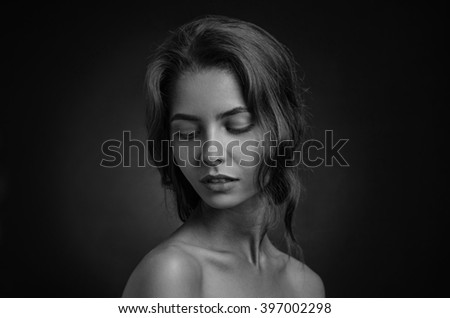 Dramatic portrait of a girl theme: portrait of a beautiful lonely girl isolated on a dark background in studio shot black and white portrait - stock photo