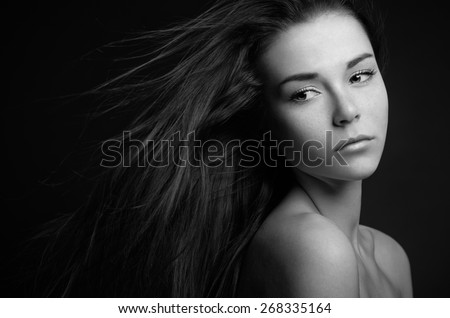 Dramatic portrait of a girl theme: portrait of a beautiful lonely girl with flying hair in the wind isolated on dark background in studio - stock photo