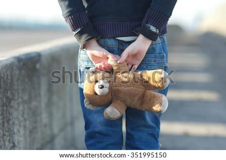 dramatic portrait of a little homeless boy holding a teddy bear, poverty, city, street - stock photo