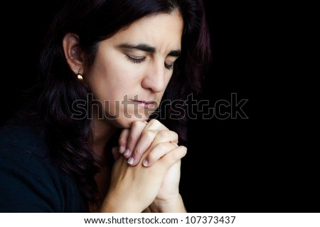 Dramatic portrait of a sad hispanic woman praying isolated on black with space for text