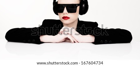 Dramatic portrait of a sexy woman in sunglasses listening to music on a set of headphones leaning on a table looking at the camera - stock photo