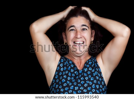 Dramatic portrait of a very angry and depressed woman screaming isolated on black with space for text - stock photo