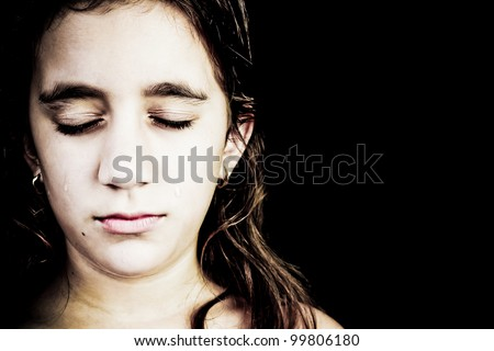 Dramatic portrait of a very sad girl crying isolated on black with space for text - stock photo