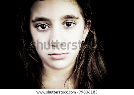 Dramatic portrait of a very sad girl crying isolated on black with space for text