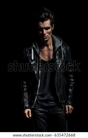 dramatic portrait of a young man in leather jacket standing on black background