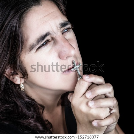 Dramatic portrait of an hispanic woman praying and kissing a crucifix (isolated on black)