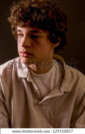 dramatic portrait of battered, beaten teen boy, crying